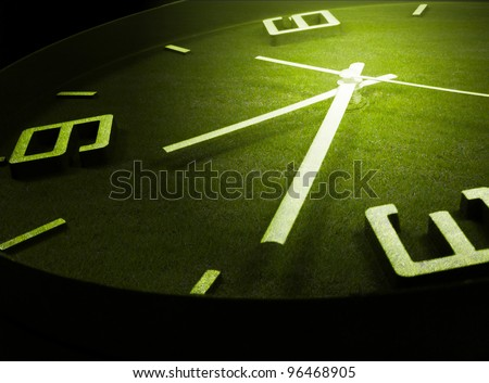 clock and green grass - stock photo