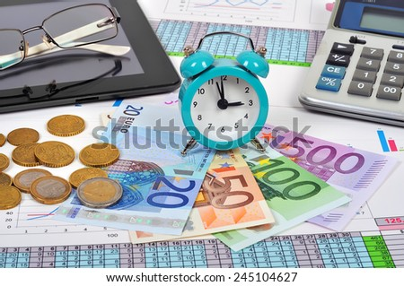 clock and money on the documents, close up