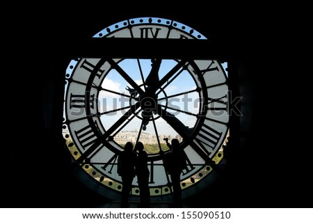 Clock at the Musee D'Orsay in Paris France. In the back we see the Sacre Coeur Basilica in Montmatre - stock photo