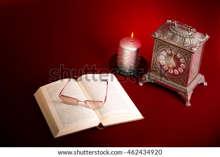Clock, book and candle on red background