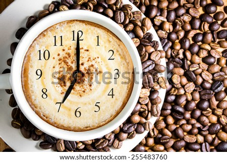 clock. cup of fresh cappuccino with clock sign, view from above  - stock photo