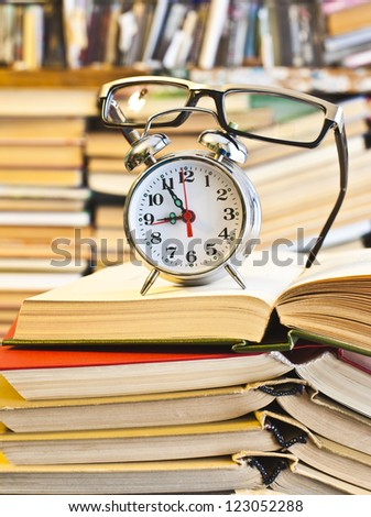 Clock, glasses, book on bookshalf  background - The idea of ??hard training, eye damage and vision of prolonged read, the need of Learning in a short time - stock photo