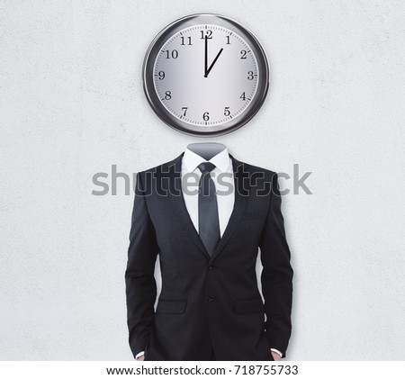 Clock headed businessman standing on concrete wall background. Accuracy concept