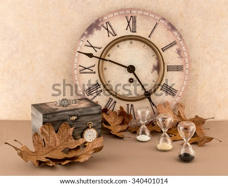 Clock, Hourglasses, Wristwatch, Pocketwatch, and Autumn Leaves - stock photo