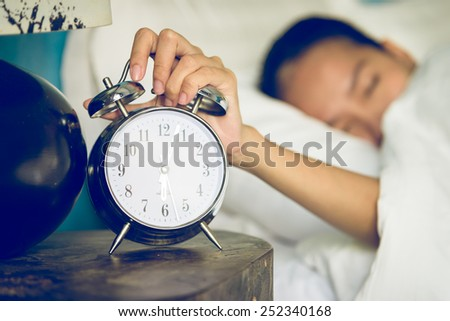 Clock in bedroom with woman sleeping - stock photo