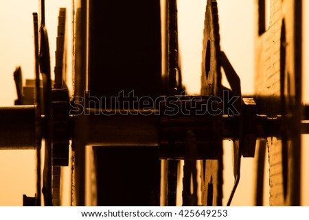 Clock mechanism on gold background. Focus on the central gears. High resolution.
