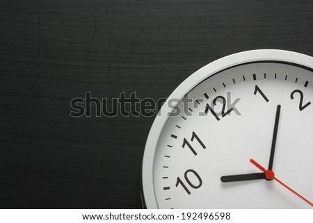 Clock on a blackboard with copy space - stock photo