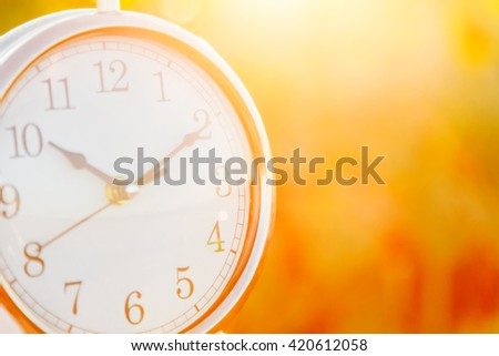 Clock on a sunset background close up. Blurred - stock photo