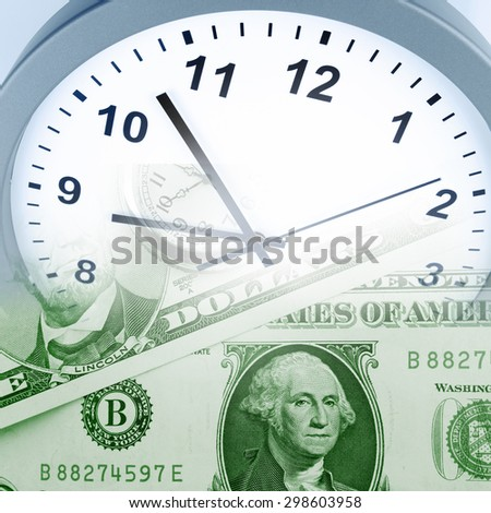 Clock on assorted American banknotes. Time is money idea - stock photo