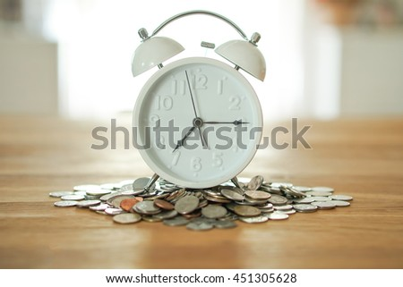 clock on coin stack, time and money concept. - stock photo