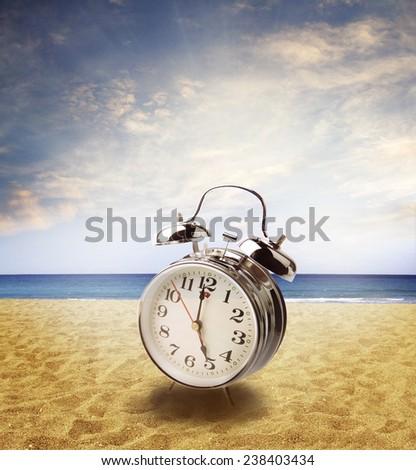 Clock on sand at beach. bright sky behind - stock photo