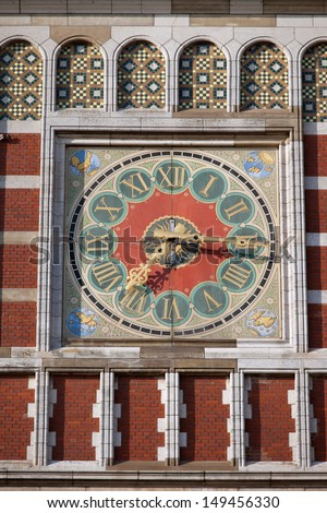 Clock on the Amsterdam Central Train Station historic facade, Holland, Netherlands - stock photo