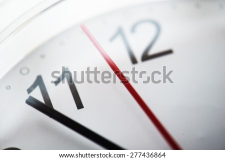 Clock or time abstract background. white clock with red and black needles. Focus is on red Around the mid point of the red needle. Intentionally shot with extremely shallow depth of field. - stock photo