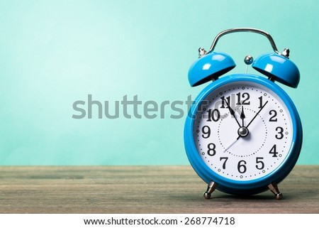 Clock. Retro alarm clock on table front mint green background - stock photo