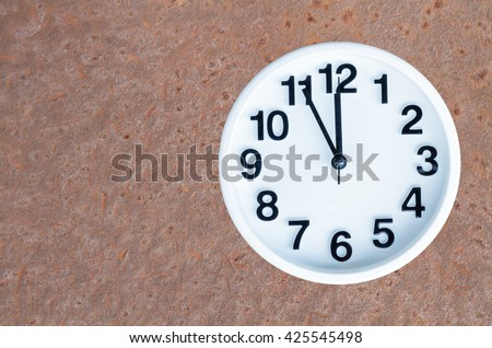 Clock show 5 minute to 12 am or pm on steel rusty background with copy space. clipping path in picture. - stock photo