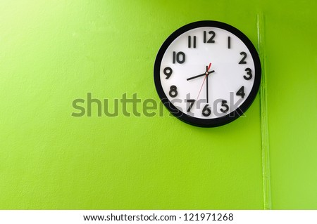 Clock showing 8:30 o'clock on a green wall - stock photo