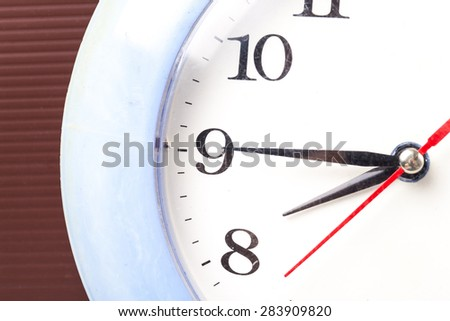 Clock showing 8 o'clock on a wooden wall - stock photo