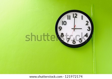Clock showing 3 o'clock pm on a green wall - stock photo