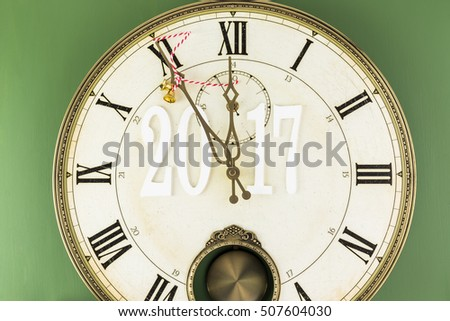 Clock shows five minutes till New Year. Minute hand of clock decorated bells with ribbon.