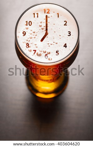 clock symbol on foam in beer glass on black table, view from above - stock photo