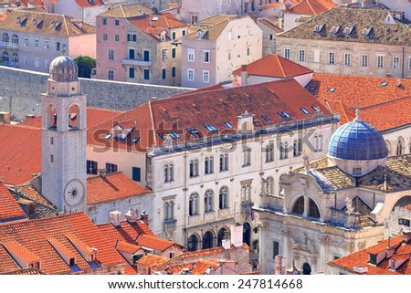 Clock tower and the church of St Blaise surrounded by orange roofs in the old town of Dubrovnik, Croatia - stock photo