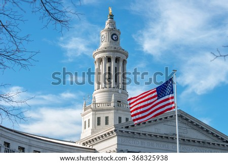 Clock Tower of Denver City Hall - A close-up view of the clock tower, topped with a golden eagle, of Denver City and County Building, with a US flag flying at front. Denver, Colorado, USA. - stock photo