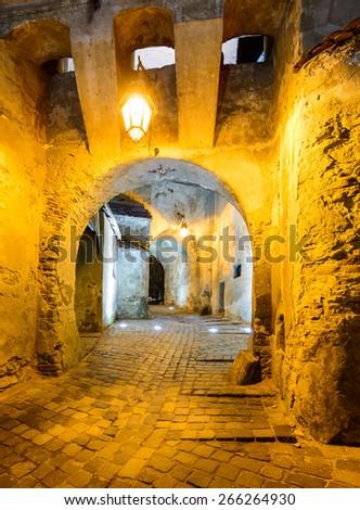 Clock tower passage in Sighisoara, Transylvania, Romania at night - stock photo