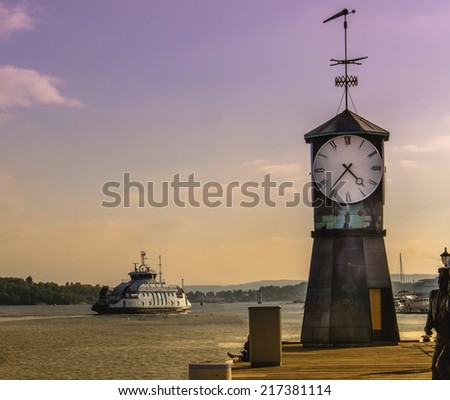 Clock tower with Oslo fjord viewed from harbor of Oslo, Norway - stock photo