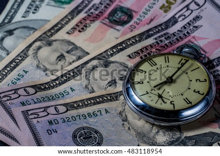 Clock watch on money - fifty dollar bills - concept image - time is money - growth over time