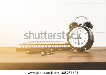 Clock with pen and notebook on wood table, still life - stock photo