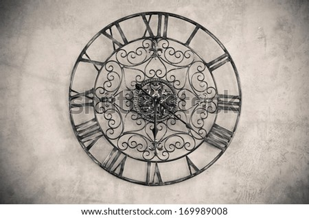 Clock with roman numbers  on the wall. Processed with vintage style. - stock photo