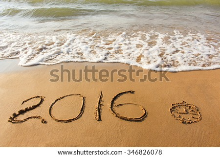 clock, 2016 year written on sandy beach sea  - stock photo