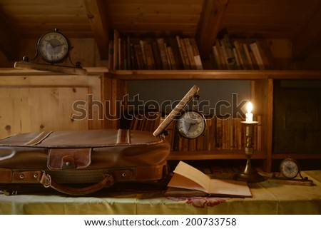 clocks floating above a suitcase and travel books, time concept - stock photo