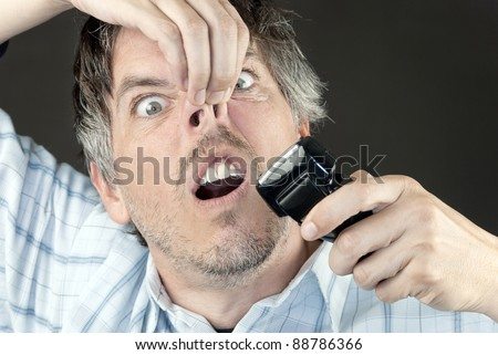 Cloe-up of a man attempting to trim his nose hair with a full sized electric razor. - stock photo