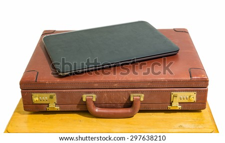 close black laptop and old vintage brown briefcase on wood table isolated - stock photo
