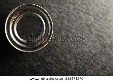 Close canned food put on the black color leather surface background represent the food      packaging and containing material technology related. - stock photo