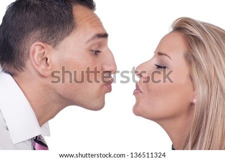 Close cropped portrait of the faces of a young man and woman preparing to kiss leaning towards each other with their lips puckered, isolated on white - stock photo