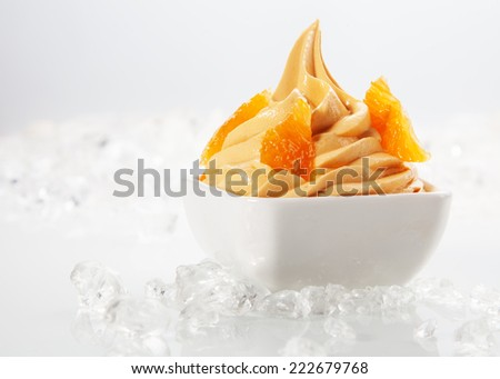 Close Delicious Yellow Frozen with Tasty Toppings on White Bowl Surrounded by Ice. Served on White Table. - stock photo