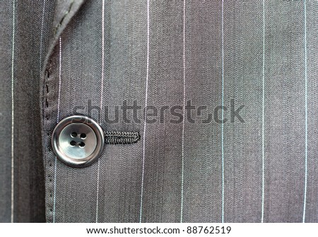 Close detail of a button on a pin striped business suit coat