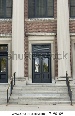 Close detail of the front doors of a columned building.