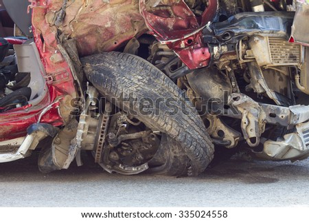 Close down the front of the red car is wrecked in an accident collision crumpled steel wheel tire burst. - stock photo