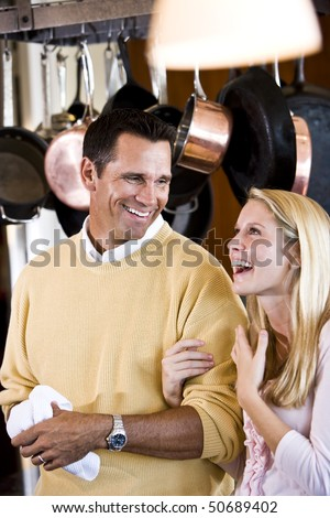 Close father and teenage daughter talking and laughing together in kitchen - stock photo