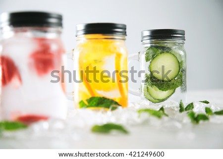Close focus on last jar Healthy fresh cool homemade lemonades with sparkling water strawberry, cucumber,mint and orange isolated in smashed ice cubes on wooden table - stock photo