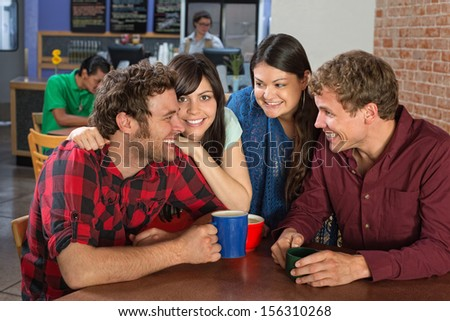 Close friends laughing in a coffee house - stock photo