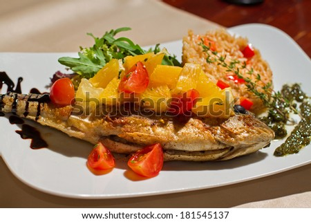 Close image of tasty fish with rise and vegetables