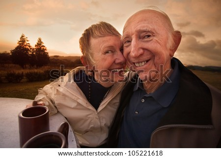 Close mature couple outside with coffee mugs - stock photo