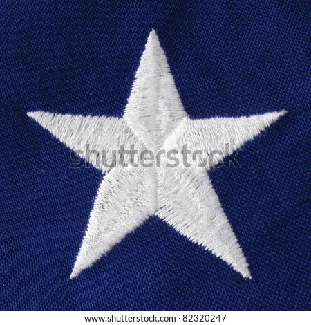Close of a crisp white embroidered star on a US Veteran's flag - stock photo