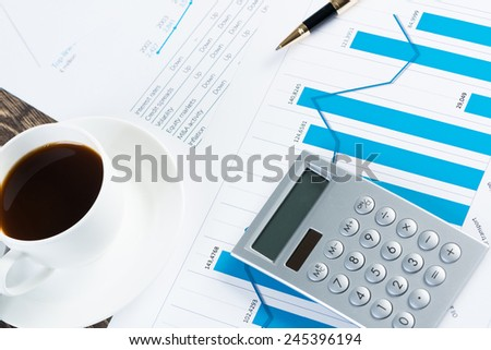 Close of business workplace with financial reports and office stuff - stock photo