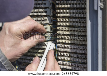 Close of hand punching down circuit panel used for phones. Using a punch down tool punch the wires down into the blades built into the communication circuit for analog phones.