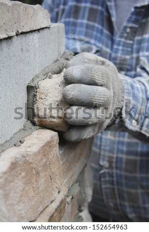 Close on a Mason's hand working on a project/Masonry/Close on a Bricklayer's hand as he smooths wet cement on a brick wall.